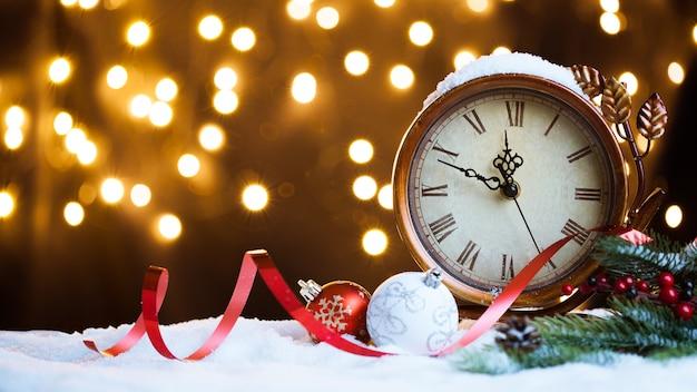 Reloj de año nuevo y adornos cubiertos con luces tarjeta de navidad