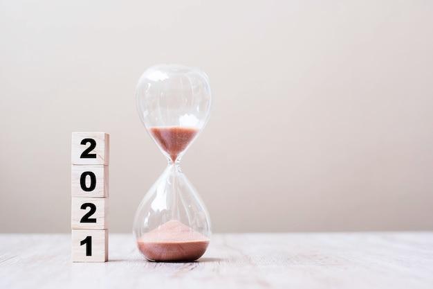 Reloj de arena con 2021 bloques de cubos de madera en la mesa
