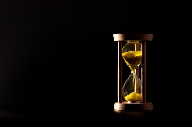 Reloj de arena aislado sobre fondo oscuro