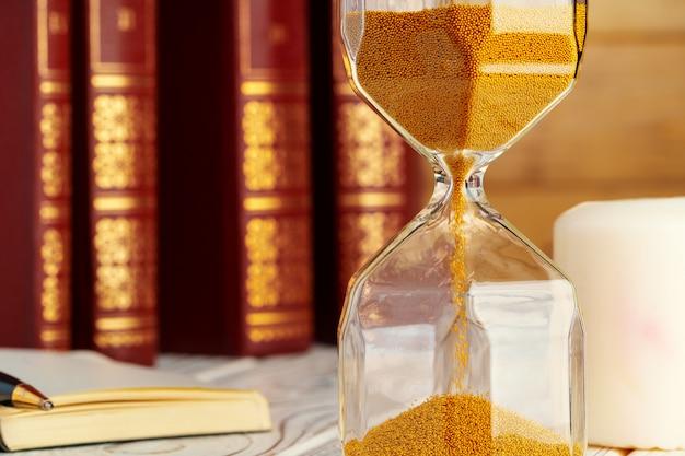 Reloj de arena de arena dorada de cerca en la mesa de trabajo