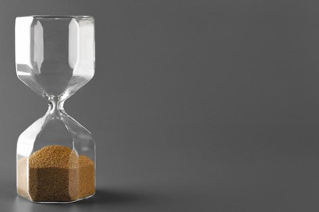 Reloj de arena con arena gris de cerca