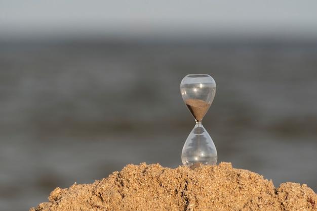 Reloj de arena en la arena del mar. concepto de tiempo.