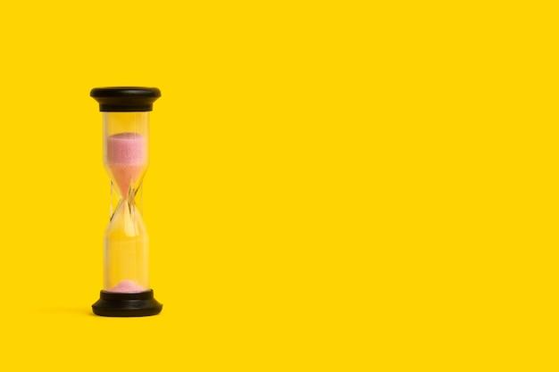 Un reloj de arena con arena rosa con espacio de copia.