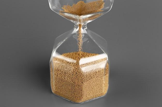 Reloj de arena con arena sobre la superficie gris de cerca