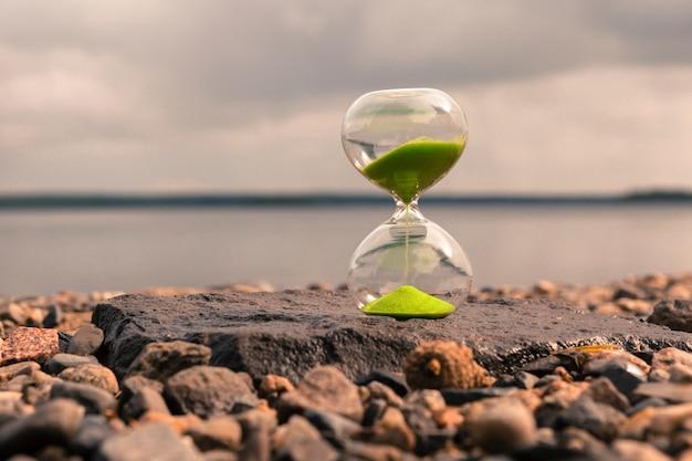 Reloj de arena con arena verde en el lago, de pie sobre pequeñas piedras. concepto de tiempo