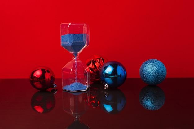 Reloj de arena y bolas de navidad contra rojo