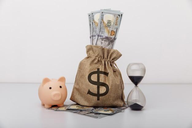 Reloj de arena con bolsa de dinero y hucha. concepto de inversión y ahorro financiero