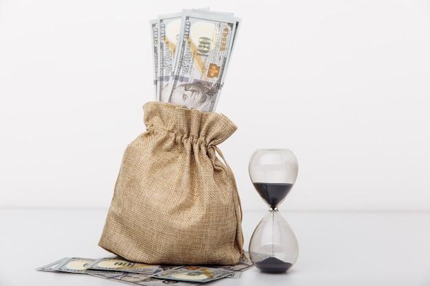 Reloj de arena con bolsa de dinero sobre fondo blanco. concepto de inversión y ahorro de finanzas.