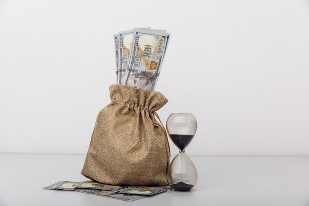 Reloj de arena con bolsa de dinero sobre fondo blanco tiempo para invertir concepto