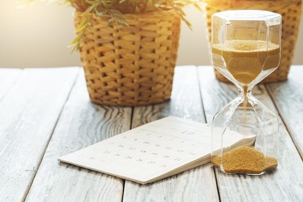 Reloj de arena con calendario en el escritorio de madera de cerca. concepto de tiempo