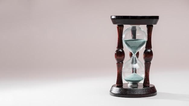 Reloj de arena como concepto de pasar el tiempo para el plazo de negocios en el fondo de color