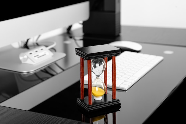 Reloj de arena con computadora en la mesa en la oficina