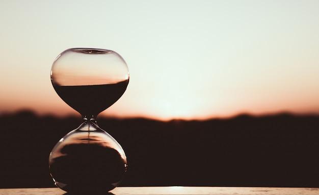 Reloj de arena contra el cielo del atardecer, fotografía artística
