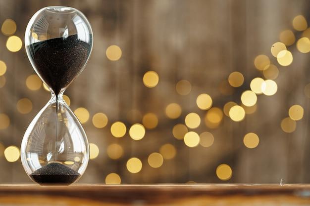 Reloj de arena en el escritorio de madera contra el fondo de luces borrosas