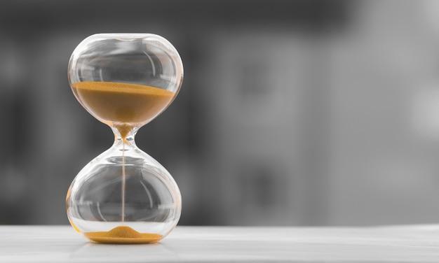Reloj de arena en un fondo borroso blanco negro. el tiempo es dinero.