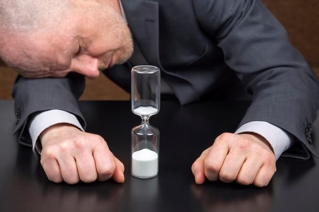 Reloj de arena junto a las manos de un hombre de negocios. tiempo de negocios. planificación de objetivos de éxito