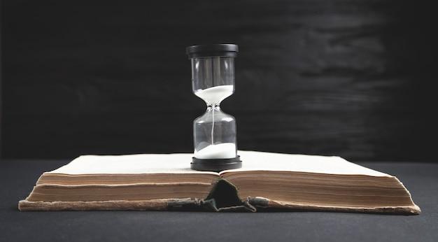 Reloj de arena y libro sobre fondo negro.