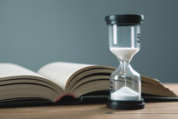 Reloj de arena con libros sobre la mesa