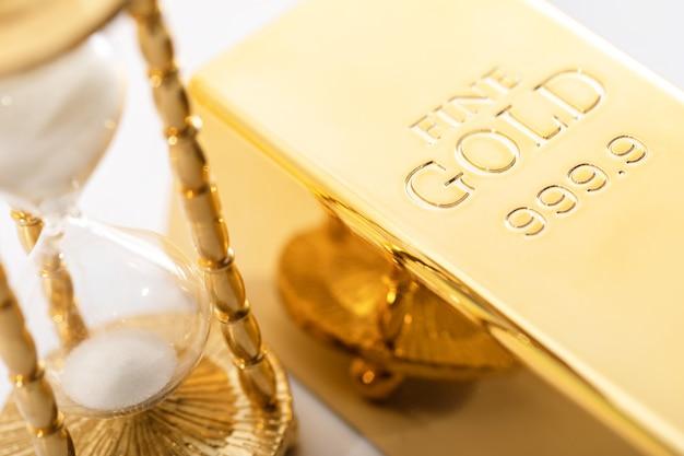 Reloj de arena y lingotes de oro fino. concepto de inversión en los materiales preciosos.