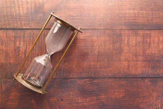 Reloj de arena en la mesa, arena que fluye a través del bulbo del reloj de arena