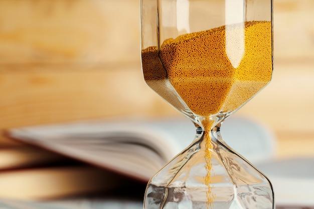 Reloj de arena en la mesa de madera con libro abierto de cerca