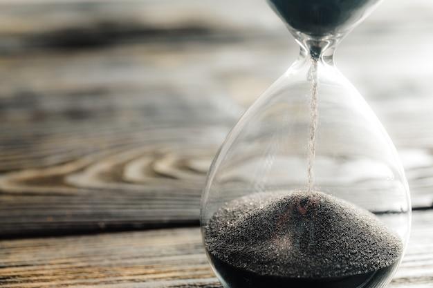 Reloj de arena moderno sobre superficie de madera