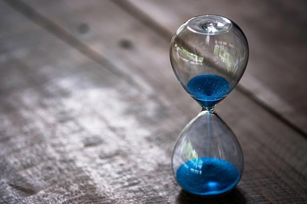 Reloj de arena o reloj de arena sobre mesa de madera.