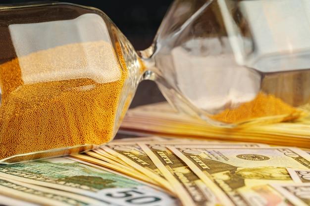 Reloj de arena en la pila de billetes de dólar de cerca