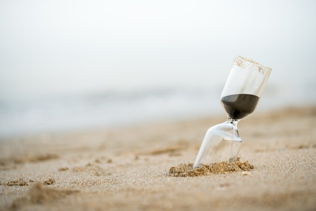 Reloj de arena en la playa, gestión del tiempo comercial