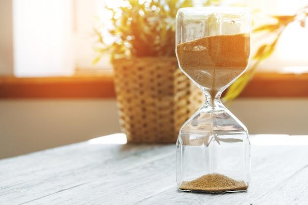 Reloj de arena en primer plano de madera bakground. concepto de tiempo