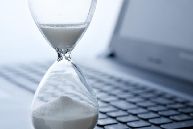 Reloj de arena en primer plano y teclado portátil, concepto de tiempo en línea.