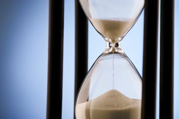 Reloj de arena que mide el tiempo que pasa sobre azul