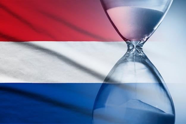 Reloj de arena sobre la bandera de los países bajos