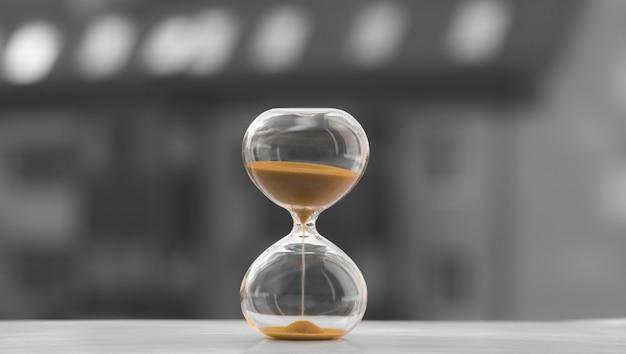 Reloj de arena sobre un fondo blanco y negro de una casa borrosa, hora de comprar una casa. la arena se está quedando sin tiempo.