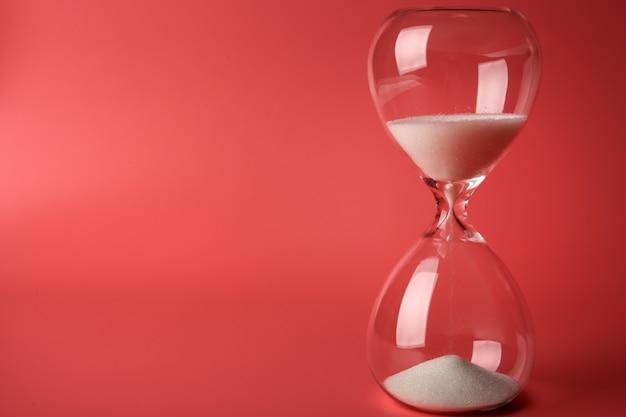 Reloj de arena sobre fondo rosa
