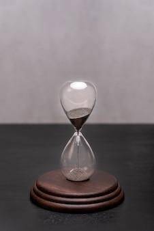 Reloj de arena sobre un soporte. se acaba el tiempo. concepto de gestión del tiempo. vertical.