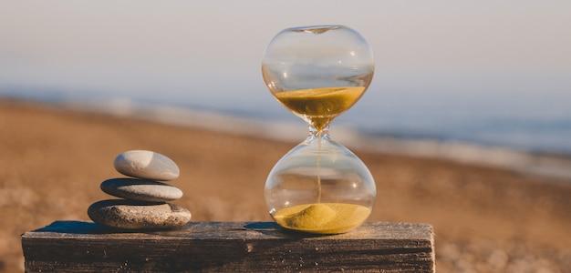 Reloj de arena sobre una tabla de madera con tres piedras en forma de pirámide, un reloj de arena moderno en una playa con arena dorada contra el fondo del mar