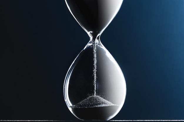 Reloj de arena en la superficie oscura