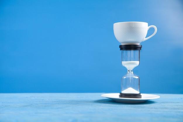 Reloj de arena y taza de café sobre fondo azul.