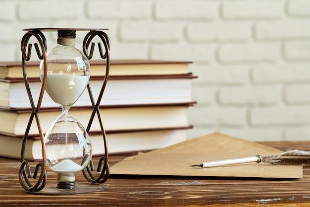 Reloj de arena vintage contra una pila de libros antiguos
