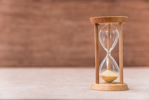 Reloj de arena vintage en la mesa de madera