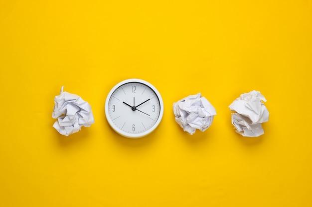 Reloj con bolas de papel arrugado sobre una superficie amarilla. vista superior