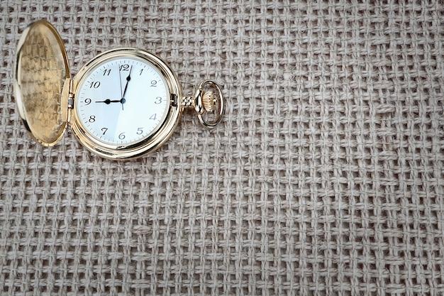 Reloj de bolsillo antiguo con arpillera texturizada. de cerca.