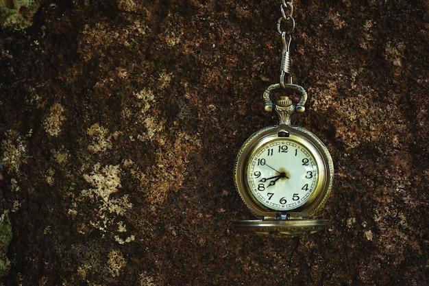 Reloj de bolsillo antiguo vintage colgado en la pared de roca