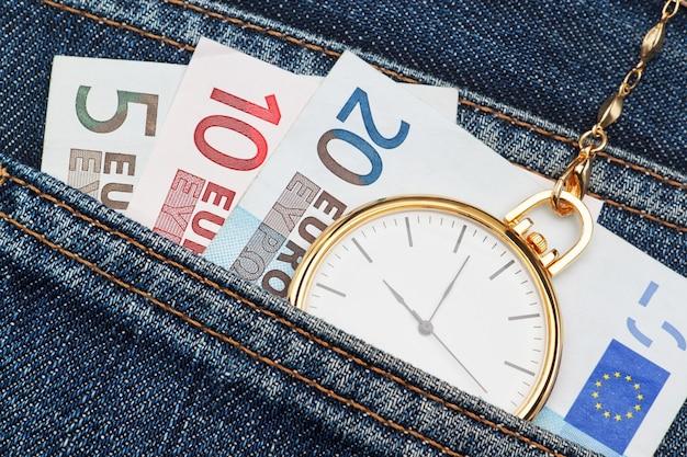 Reloj de bolsillo con cadena en jeans y dinero euro. de cerca.