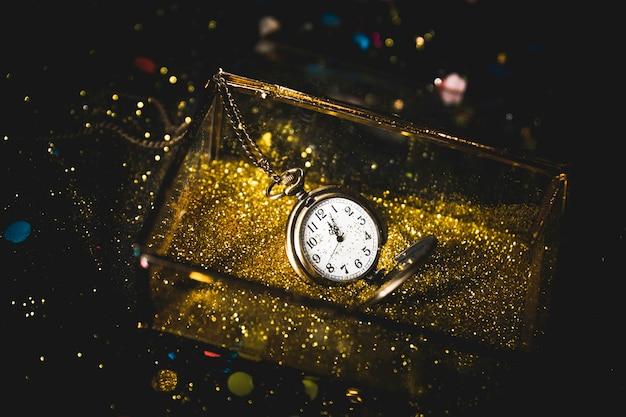 Reloj de bolsillo en caja con lentejuelas.