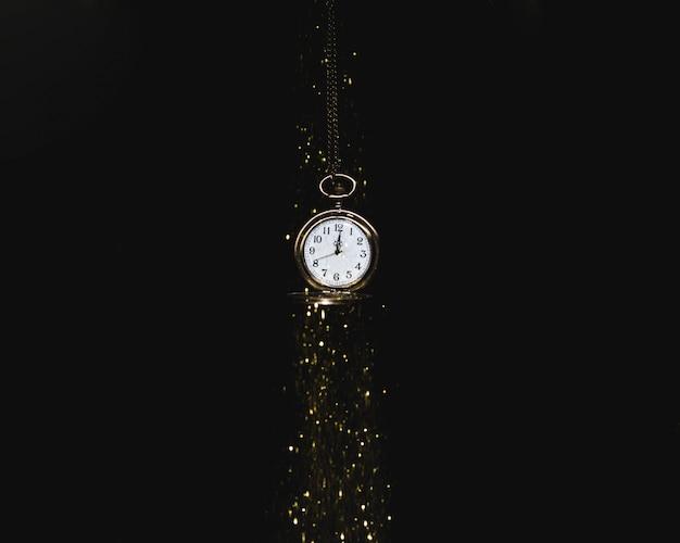 Reloj de bolsillo colgante bajo lentejuelas que caen.
