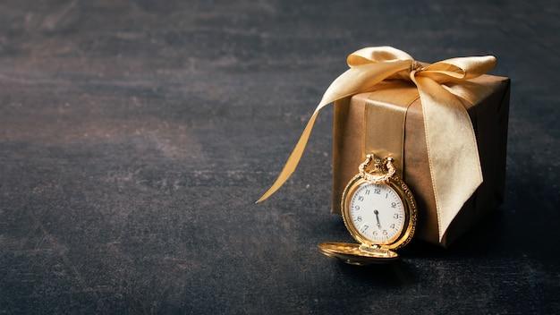 Reloj de bolsillo dorado y papel artesanal de regalo.