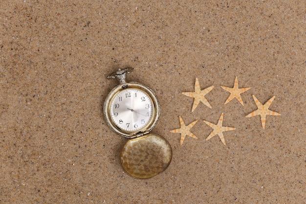 Reloj de bolsillo dorado perdido en la arena con estrella de mar. vista superior