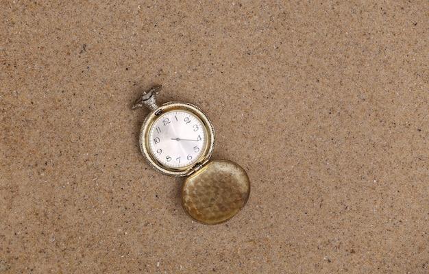 Reloj de bolsillo dorado perdido en la arena. vista superior